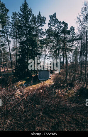 Two small cottages in the forest near the shore of Lauttasaari Helsinki Finland on a sunny spring day - Stock Photo