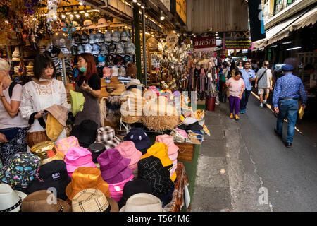 Thailand, Bangkok, Chinatown, Yaowarat, Sampeng Lane market, Soi Wanit 1, hat shop shoppers browsing in shops lining walking street - Stock Photo
