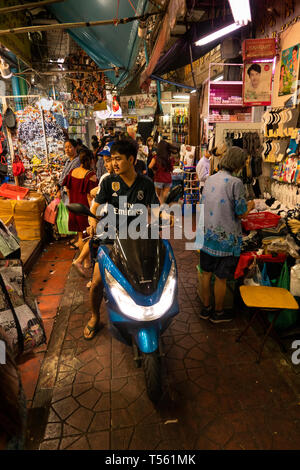 Thailand, Bangkok, Chinatown, Yaowarat, Sampeng Lane market, Soi Wanit 1, young couple riding motorcycle through crowded walking street - Stock Photo