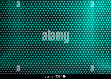 green light through perforated bent metal sheet - Stock Photo