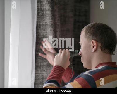 Man looks out the window with binoculars - Stock Photo