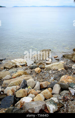 Big rocks near still, calm sea at touristic place Toroni in Sithonia,  Chalkidiki peninsula, rocky beach in Greece early in the morning - Stock Photo