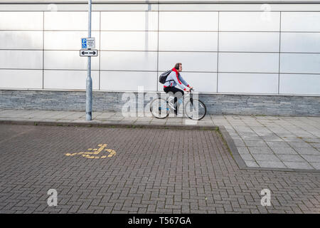 Man wearing headphones and carrying a backpack cycling on a path past a disabled parking bay - Stock Photo