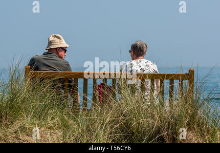 two elderly people or an older retired couple sitting on a wooden bench at the seaside in the summertime. - Stock Photo