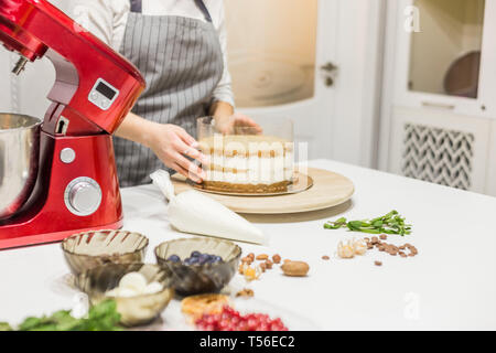 Young female confectioner whips cream in a metal bowl in a red electric mixer. The concept of homemade pastry, cooking. - Stock Photo