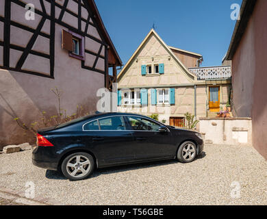 Bergheim, France - 19 Apr 2019: Luxury black Volvo limousine car parked in front of typical Alsatian house  - Stock Photo