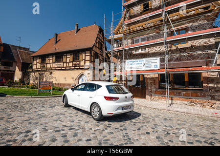 Bergheim, France - 19 Apr 2019: White Seat Leon driving on the old paved cobblestone street in the center of French village of Bergheim  - Stock Photo