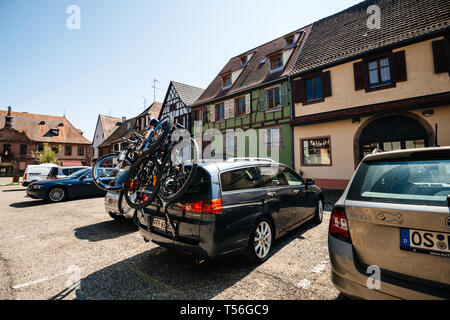 Bergheim, France - 19 Apr 2019: Tourist car with multiple Bikes on the trailer parked in front of the city-hall main place  - Stock Photo