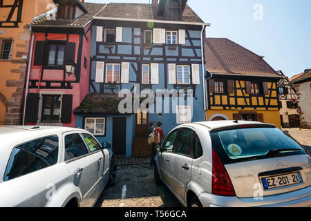 Bergheim, France - 19 Apr 2019: Young couple taking photos in front of the colorful half-timbered houses in central part of the village - Stock Photo
