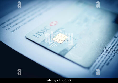 Paris, France - Apr 9, 2017: Close-up focus with tilt-shift lens over New HSBC French division featuring Arc de Triumph on the cover Visa Maestro card received and instruction how to use it contactless security chip - Stock Photo