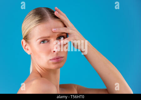 Signs of aging. Portrait of shocked young woman is looking at camera with disappointedly while touching her wrinkles on forehead on blue background - Stock Photo