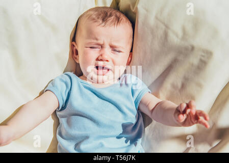Baby lying in the sun angry and crying calling his parents. - Stock Photo