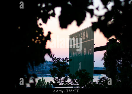 Freeway street sign in a city with sunrise in background. Framed by trees - Stock Photo