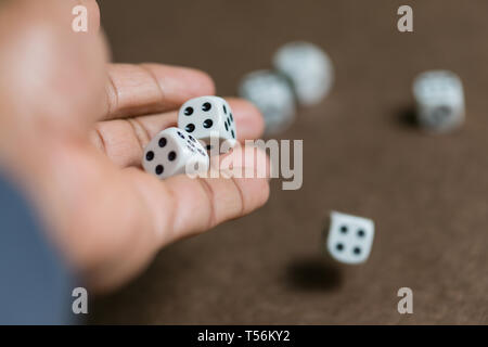 Man hand roll dice on board - Stock Photo
