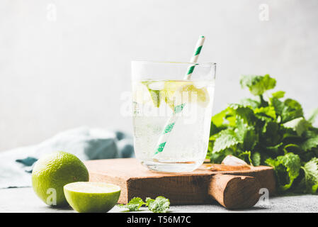 Sparkling summer cocktail with lime and mint or soda water with lime. Ice cold refreshing summer drink in glass with drinking cocktail tube - Stock Photo