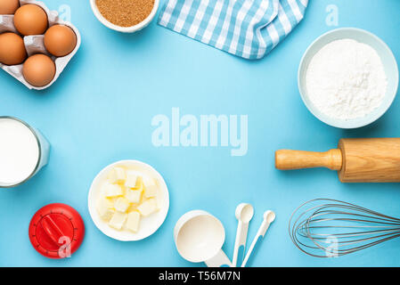 Baking utensils and ingredients on blue background. Eggs, butter, kitchen utensils, sugar, milk and flour. Recipe mock up, bakery background with copy - Stock Photo