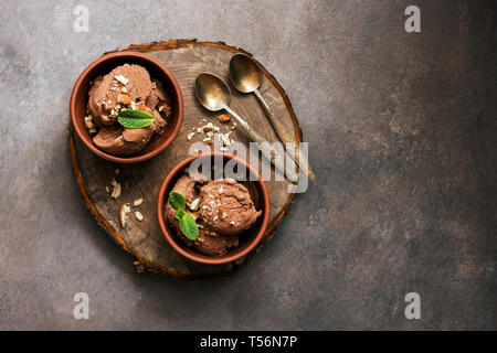 Homemade chocolate ice cream with mint and nuts in bowls on a stump cutting board, dark rustic background. Overhead view, copy space - Stock Photo