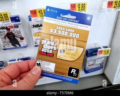 PLATTSBURGH, USA - JANUARY 21, 2019 : Cash card of Grand Theft Auto video game in a hand of a buyer at Walmart store. - Stock Photo