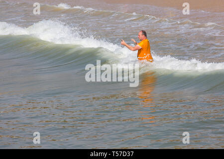 Bournemouth, Dorset, UK. 22nd Apr, 2019. UK weather: after a hazy start the glorious weather continues with hot and sunny weather, as beachgoers head to the seaside to enjoy the heat and sunshine at Bournemouth beaches on Easter Monday before the weather changes and the return to work. Man takes selfies jumping in the waves in the sea. Credit: Carolyn Jenkins/Alamy Live News - Stock Photo