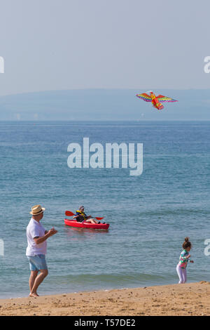 Bournemouth, Dorset, UK. 22nd Apr, 2019. UK weather: after a hazy start the glorious weather continues with hot and sunny weather, as beachgoers head to the seaside to enjoy the heat and sunshine at Bournemouth beaches on Easter Monday before the weather changes and the return to work. Flying a kite. Boy in kayak. Credit: Carolyn Jenkins/Alamy Live News - Stock Photo