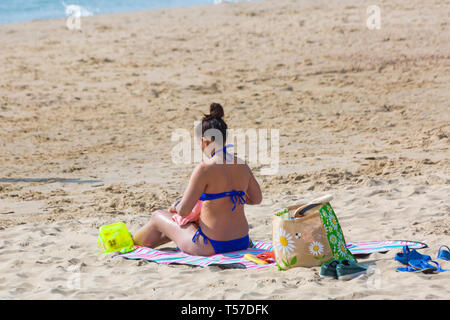 Bournemouth, Dorset, UK. 22nd Apr, 2019. UK weather: after a hazy start the glorious weather continues with hot and sunny weather, as beachgoers head to the seaside to enjoy the heat and sunshine at Bournemouth beaches on Easter Monday before the weather changes and the return to work. Woman in blue bikini sunbathing at the beach. Credit: Carolyn Jenkins/Alamy Live News - Stock Photo