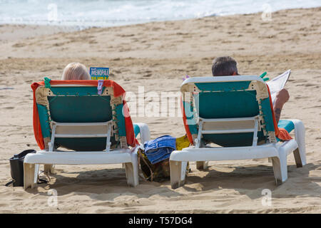 Bournemouth, Dorset, UK. 22nd Apr, 2019. UK weather: after a hazy start the glorious weather continues with hot and sunny weather, as beachgoers head to the seaside to enjoy the heat and sunshine at Bournemouth beaches on Easter Monday before the weather changes and the return to work. Couple sunbathing on sun loungers reading. Credit: Carolyn Jenkins/Alamy Live News - Stock Photo