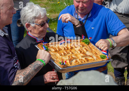 """Hallaton, Leicestershire. 22nd April 2019. Hare Pie Scramble & Bottle Kicking, this is an ancient custom in two distinct parts. The first is a procession, baskets of bread and the eponymous Hare Pie (believed to be minced beef these days), once at the church gate, the pie is blessed and distributed to the crowds and the second is a mass """"ballgame"""" played with small wooden casks called bottles between the villages of Hallaton and Melbourne. Credit: Keith J Smith./Alamy Live News - Stock Photo"""