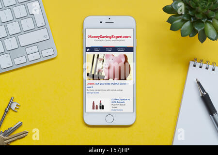 An iPhone showing the Money Saving Expert website rests on a yellow background table with a keyboard, keys, notepad and plant (Editorial use only). - Stock Photo