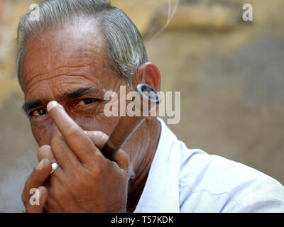 Middle-aged Indian Rajasthani man smokes tobacco in his chillum pipe in public. - Stock Photo