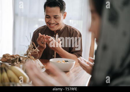 muslim man open his arm and pray before eat - Stock Photo