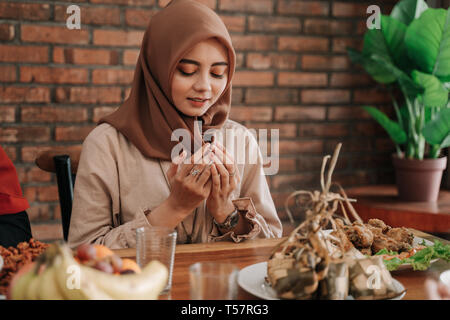 woman open her palm and pray before eating - Stock Photo
