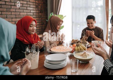 muslim people praying before having their food - Stock Photo