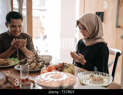 muslim people praying before break fasting - Stock Photo