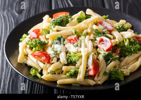 Dietary pasta Casarecce with vegetables dressed with creamy cheese sauce close-up on a plate on the table. horizontal - Stock Photo