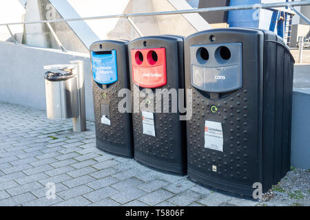 Council Recycling bins for plastic bottles, cans, and newspapers and magazines, with a litter bin, outside the Sage, Gateshead, Tyne and Wear, UK - Stock Photo