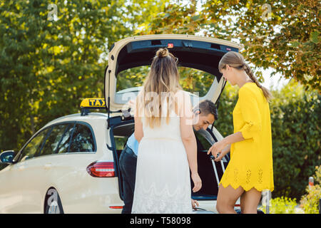 Taxi driver putting luggage of women in trunk of car - Stock Photo