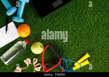 Sport equipment. Creative flat lay of sport and fitness equipment on green grass. View from above. Flat lay. Place under the text. Copy space. - Stock Photo