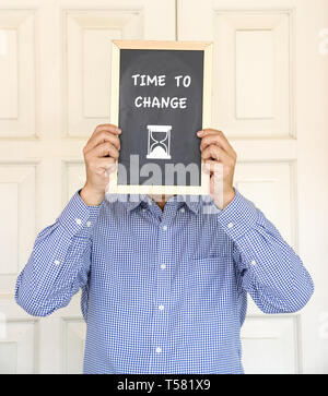 Time to change, words and a time on a black board in front of a man's face - Stock Photo