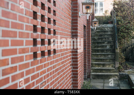 Red bricked wall with village view and grungy stairs - Stock Photo