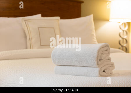 White towel on bed in hotel room - Stock Photo