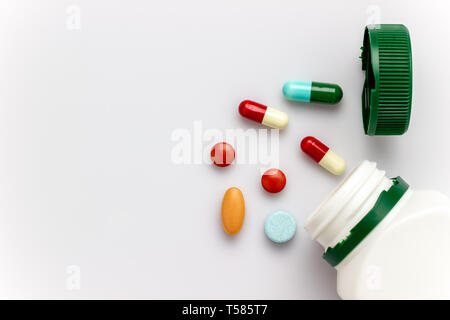 Multicoloured capsules with white medicine bottles and green caps on white background. Copy space for text or articles. Concepts of health and medicin