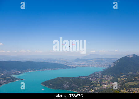 Man Hand-gliding over Mointains on a Hot Summer Day - Stock Photo