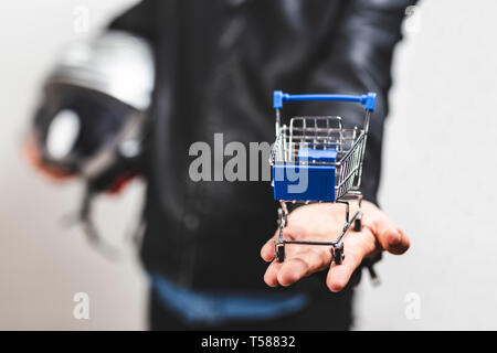 Delivery man standing and holding a mini shopping cart - The delivery service concept - - Stock Photo