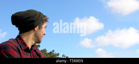 Caucasian hipster man looking away banner with blue sky and clouds. - Stock Photo