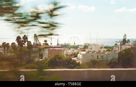 A big Ferris wheel among many white villas and palm trees in Agia Napa, Cyprus. Vast blue sea on the horizon. Warm day in autumn - Stock Photo