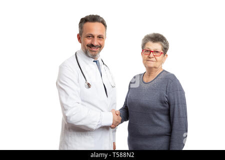 Friendly male doctor and elderly patient woman shaking hands as greeting or deal concept isolated on white - Stock Photo
