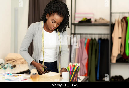 Fashion designer working in studio, cutting drawing - Stock Photo