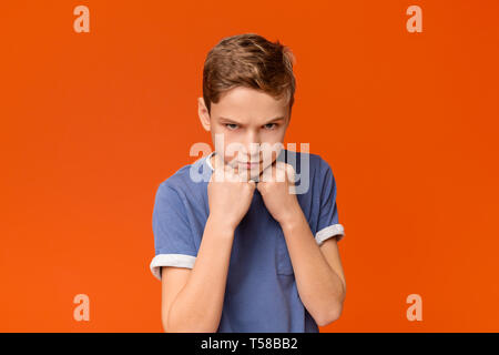 Teen boy clenching fists, ready to fight - Stock Photo