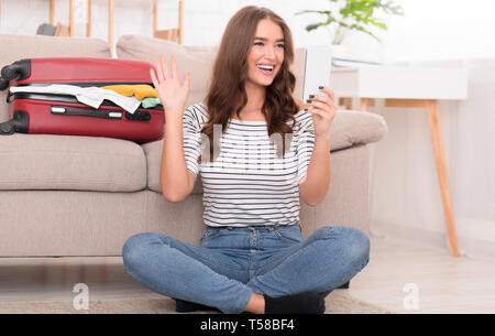 Woman making video call, sitting near valise, waiting for vacation - Stock Photo