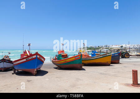 Quaint fishing village of Arniston, Agulhas, Western Cape, South Africa, Colourful traditional wooden  fishing boats ashore in the harbour on a windy  - Stock Photo